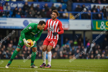 Accrington Stanley Forward, Jonathan Edwards (24) closes down Portsmouth Goalkeeper, David Forde (1) during the EFL Sky Bet League 2 match between Portsmouth and Accrington Stanley at Fratton Park, Portsmouth