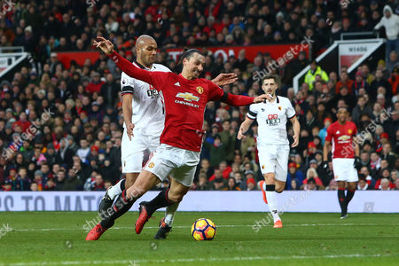 Younes Kaboul of Watford bundles over an offside Zlatan Ibrahimovic of Manchester United during the Premier League match between Manchester United and Watford played at Old Trafford, Manchester on 11th February 2017