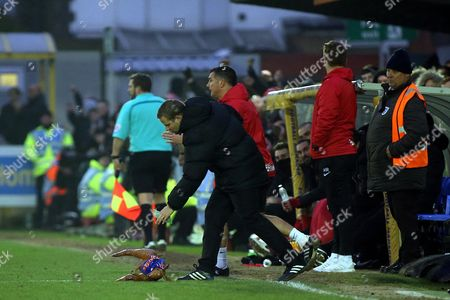 4th Official, Mr T Ramsey, picks up an object thrown from the crowd during AFC Wimbledon vs Charlton Athletic, Sky Bet EFL League 1 Football at the Cherry Red Records Stadium on 11th February 2017