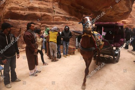 """Bollywood star Tiger Shroff, second left, watches a horse cart pass while filming his new movie, """"Munna Michael,"""" in Jordan's iconic Petra archaeological site. Shroff, rising female lead Sana Saeed and an Indian cinema crew are filming across Jordan for the film directed by Sabir Khan"""