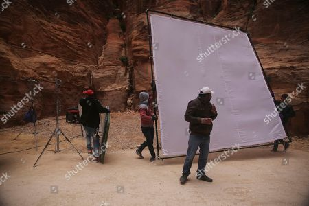 """A film crew carries equipment through Jordan's iconic rock canyon during the filming of the Bollywood movie, """"Munna Michael,"""" in Jordan's iconic Petra archaeological site. Film star Tiger Shroff and his co-star Sana Saeed and an Indian cinema crew are filming across Jordan for the film directed by Sabbir Khan"""