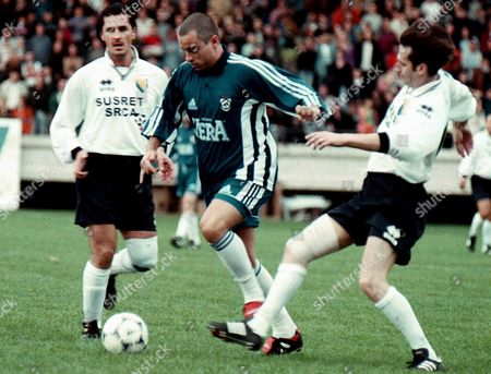 Sarajevo Bosnia and Hercegovina: Italian Star Singer Eros Ramazotti (c) Finds His Way Through Two Unidentified Bosnian Defenders During a Charity Soccer Match in Sarajevo 19 October 1998 to Raise Funds For Demining Operations Around Schools in Bosnia