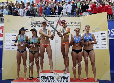 Stock Photo of Brazilians Franca Larissa and Juliana Felisberta Da Silva (c) Hold Swords As They Pose on the Podium After Winning the Women's Beach Volleyball Grand Slam in Stavanger Norway 03 July 2010 Maria Antonelli and Talita Antunes Da Rocha (l) From Brazil Got the Second Place with May-treanor Misty and Nicole Branagh From the United States at Third Norway Stavanger