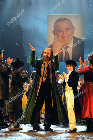 Rowan Atkinson as Fagin in front of a picture of Lionel Bart