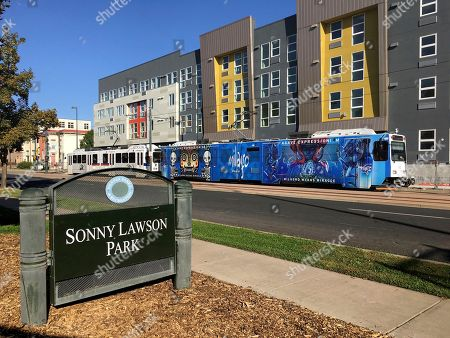 """A sign identifying Sonny Lawson Park sits while a commuter rail passes in Denver's Five Points neighborhood. The historic black neighborhood was once called """"The Harlem of West,"""" a place where Billie Holiday, Count Basie and Miles Davis performed and novelist Jack Kerouac tried to capture the spirit of the bebop movement in """"On The Road"""