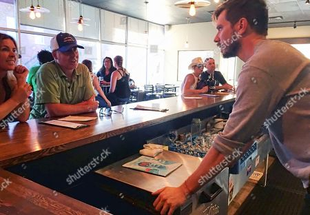 """Austin Wiley, right, owner of Spangalang Brewery, talks to patrons at the bar in Denver's Five Points neighborhood. The historic black neighborhood was often called """"The Harlem of West,"""" a place where Billie Holiday, Count Basie and Miles Davis performed and novelist Jack Kerouac tried to capture the spirit of the bebop movement in """"On The Road."""" The brewery's name, Spangalang, is the term used to describe the bread and butter jazz cymbal rhythm"""