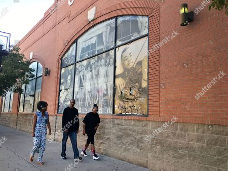 """Pedestrians walk past historic photographs celebrating Denver's Five Points, a neighborhood that was called """"The Harlem of West,"""" in Denver, Colo. Five Points is where Billie Holiday, Count Basie and Miles Davis performed and novelist Jack Kerouac wrote part of """"On The Road."""" The historic black neighborhood is facing gentrification with new breweries and coffee shops near buildings that once housed jazz clubs and consequential black-owned businesses"""