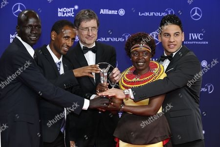Olympic Refugee Team members Yiech Pur Biel (L), Ramis Anis (2-L), an unidentified person (C), Kenian Tegla Loroupe (2-R) and Yonas Kinde pose with the 'Laureus Sport of Good Award for Sporting Inspiration of the Year' award at the Laureus Sport Awards in Monaco, 14 February 2017. The Laureus Media Prize is attributed to people that have made an impact to the world of sport.