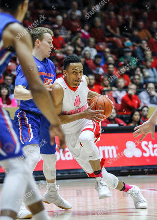 New Mexico's Elijah Brown (4) drives around Boise State's David Walker (55) during the first half of an NCAA college basketball game in Albuquerque, N.M