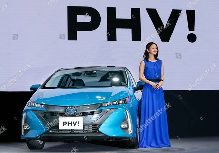 Actress Satomi Ishihara poses with a Toyota new Prius PHV during a press conference rolling out new Prius PHV plug-in hybrid in Tokyo, . Toyota has revamped its plug-in hybrid with a longer cruise range and quicker charging, including from a regular home plug, hoping it will sell better than the first model from five years ago that officials acknowledged had flopped
