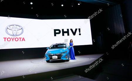 Japanese actress Satomi Ishihara poses with a Toyota new Prius PHV during a press conference rolling out new Prius PHV plug-in hybrid in Tokyo, . Toyota has revamped its plug-in hybrid with a longer cruise range and quicker charging, including from a regular home plug, hoping it will sell better than the first model from five years ago that officials acknowledged had flopped