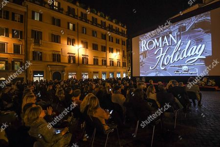 People Watch the Film 'Roman Holiday (vacanze Romane)' For the Celebration of the Centenary of the Birth of Gregory Peck at the Spanish's Square (piazza Di Spagna) in Front of the Spanish Steps (scalinata Di Trinit? Dei Monti) in the Centre of Rome Italy 18 October 2016 Roman Holiday is a 1953 Us Romantic Comedy Film Directed by William Wyler It Stars Gregory Peck As a Reporter and Audrey Hepburn As a Royal Princess out to See Rome on Her Own It was Shot at the Cinecitt? Studios and on Location Around Rome During the 'Hollywood on the Tiber' Era Italy Rome