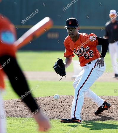 Baltimore Orioles pitcher Chris Lee fields a ball during a baseball spring training workout in Sarasota, Fla