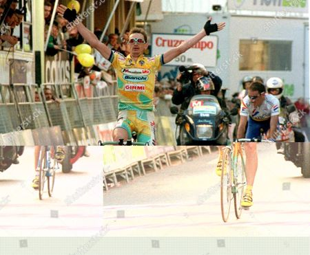 V04-19980227-valencia: Russian Cyclist Dimitro Konishev of Mercatone Team Celebrates As He Crosses the Finishing Line to Win the Fourth Stage of the Valencia Cycling Tour Over 163km From Sagunto to Segorbe 27 February Spaniard Jos Luis Arrieta (r) of Banesto Team Finished Second Place Spain Segorbe