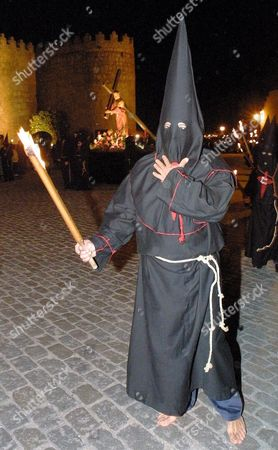 Av01 - 20020328 - Avila Spain : an Unidentified Hooded Penitent Holds a Torch During the Parade of 'Cristo De Las Batallas' (christ of the Battles) Procession in Avila Central Spain on Thursday 28 March 2002 Penitents Barefoot and Dressed in Black Paraded to Drumbeats and Carried Heavy Crosses the Hoods Are a 15th Century Easter Tradition Enabling 'Sinners' to Repent Without Being Identified Easter Processions Are Common Throughout Spain Epa Photo Efe / David Castro Barreiro Spain Avila
