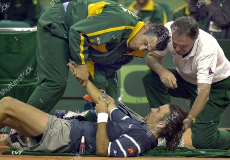 B20 - 20001208 - Barcelona Catalonia Spain : Australia's Patrick Rafter (down) Gets a Massage From an Unidentified Australian Doctor (l) After a Cramp While Team Captain John Newcombe (r) Holds His Head During Davis Cup Final Singles Tennis Match Against Spain's Juan Carlos Ferrero in Barcelona's Palau Sant Jordi Late Friday 08 December 2000 Rafter was Forced to Retire From the Match Due to His Injury Epa Photo Efe/lluis Gene Spain Barcelona