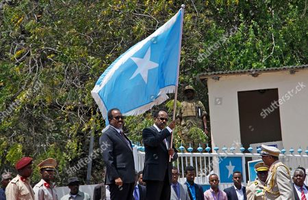 Mohamed Abdullahi Farmajo, Hassan Sheikh Mohamud Somalia's President Mohamed Abdullahi Farmajo, center-right, holds a Somali flag during a handover ceremony at the presidential palace with former president Hassan Sheikh Mohamud, center-left, in Mogadishu, Somalia . The Somalia-based extremist group al-Shabab is claiming responsibility for a mortar attack outside the presidential palace during a handover ceremony for the country's new president