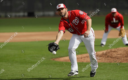 Washington Nationals relief pitcher Nick Lee tosses the ball with his glove during a spring training baseball workout, in West Palm Beach, Fla
