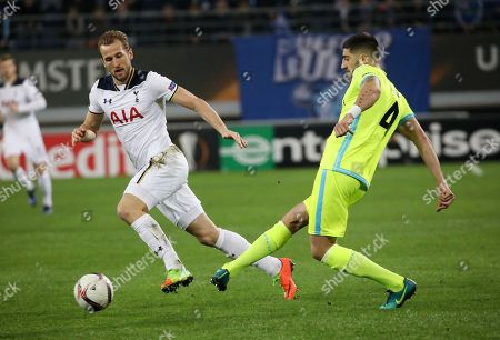 Gent's Samuel Gigot, right, challenges for the ball with Tottenham's Harry Kane during the Europa League round of 32, first leg, soccer match between KAA Gent and Tottenham Hotspur at the Ghelamco Arena in Ghent, Belgium