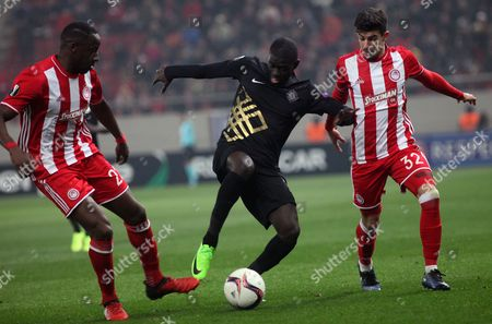 Stock Photo of Olympiacos? Thanasis Androutsos (R) and Aly Cissokho (L) vies for the ball with Osmanlispor?s Badou Ndiaye during the UEFA Europa League Round of 32 first legr match held at Karaiskaki Stadium in Athens, Greece, 16 February 2017.