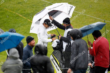 Camilo Villegas puts back his driver on the 10th tee box after play was suspended during the second round of the Genesis Open golf tournament at Riviera Country Club, in the Pacific Palisades area of Los Angeles