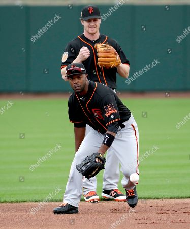 San Francisco Giants' Jimmy Rollins fields a ball as teammate Gordon Beckham watches during a spring training baseball workout, in Scottsdale, Ariz