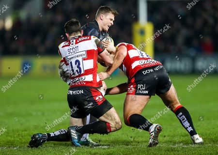 Chris Ashton of Saracens is tackled by Matt Scott of Gloucester Rugby and Paul Doran-Jones of Gloucester Rugby