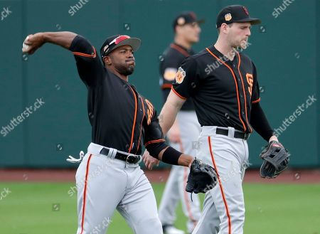 San Francisco Giants' Jimmy Rollins throws during spring training baseball workouts, in Scottsdale, Ariz