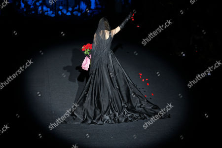 Lucia, younger sister of Spanish model Bimba Bose who died recently from cancer, throws rose petals as she displays a 2017-18 Fall/Winter long dress by Spanish designer Francis Montesinos during the Madrid's Fashion Week in Madrid