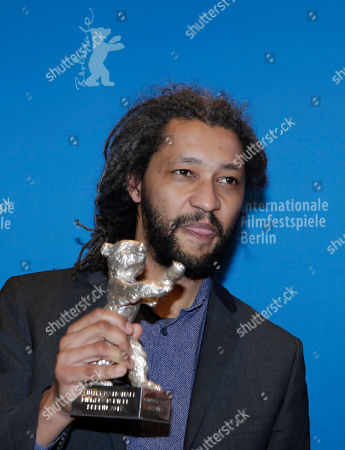 Alain Gomis poses for photographers with the Silver Bear Grand Jury Prize for 'Felicite' during the award ceremony at the 2017 Berlinale Film Festival in Berlin, Germany