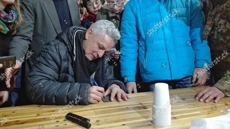 Former Italian forward Roberto Baggio signs autographs during his visit to one of the areas stricken by the earthquake on August 24 and October 26, in Norcia, Italy, 18 February 2017.
