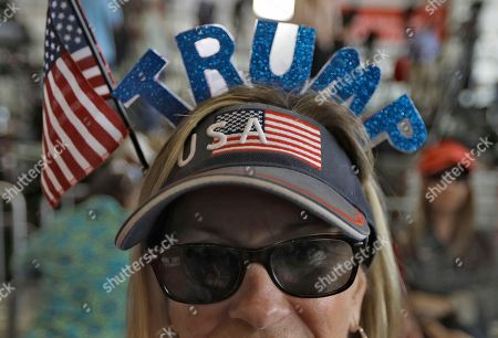 Connie Smith, of Cocoa, Fla., wears a President Donald Trump visor during a campaign rally, in Melbourne, Fla
