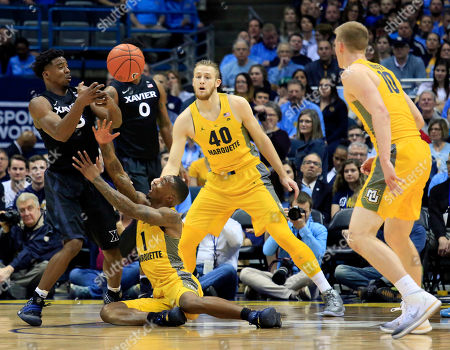 Stock Image of Quentin Goodin, Duane Wilson Xavier guard Quentin Goodin, left, battles for the ball with Marquette guard Duane Wilson, center, during the first half of an NCAA college basketball game, in Milwaukee