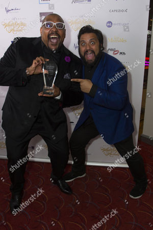 Trevor Dion Nicholas, with Nathan Amzi, accepts the award for Best Supporting Actor in a Musical for Aladdin