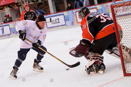 Russian jazz musician Igor Butman, left, tries to score past former NHL goaltender Frederic Cassivi, of Canada's, during an exhibition ice hockey match at the Red Square, in Moscow, Russia, on . This exhibition game was the last of three, the first game took place in Kazan and the second in St.Petersburg