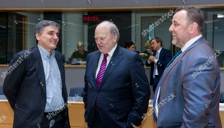 Greek Finance Minister Euclid Tsakalotos, left, is talking with the Irish Finance Minister Michael Noonan, center, and the Estonian Finance Minister Sven Sester prior to a round table meeting of Eurogroup finance ministers at the EU Council building in Brussels on . The eurozone's 19 finance ministers will be looking to defuse the risk of another Greek crisis as they try to agree Monday on what reforms Greece must still take to qualify for more loans
