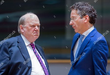 Irish Finance Minister Michael Noonan, left, is talking with the Dutch Minister of Finance, President of the Council Jeroen Dijsselbloem prior to a round table meeting of Eurogroup finance ministers at the EU Council building in Brussels on . The eurozone's 19 finance ministers will be looking to defuse the risk of another Greek crisis as they try to agree Monday on what reforms Greece must still take to qualify for more loans