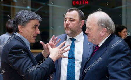 Greek Finance Minister Euclid Tsakalotos, left, is talking with the Estonian Finance Minister Sven Sester, center, and the Irish Finance Minister Michael Noonan prior to a round table meeting of Eurogroup finance ministers at the EU Council building in Brussels on . The eurozone's 19 finance ministers will be looking to defuse the risk of another Greek crisis as they try to agree Monday on what reforms Greece must still take to qualify for more loans