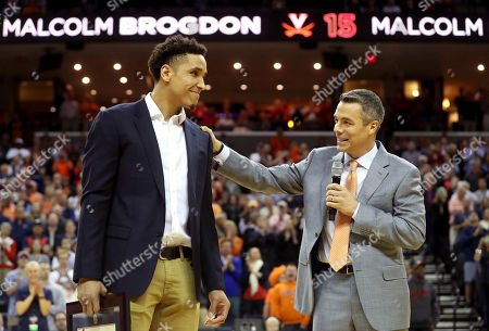 Malcolm Brogdon is recognized by Virginia head coach Tony Bennett during a ceremony to retire his number before the start of an NCAA college basketball game against Miami, in Charlottesville, Va