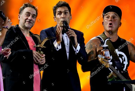 Chilean TV presenter Rafael Araneda stands between vocalist Vicentico, left, and bassist Sr. Flavio, of the Argentina rock band Los Fabulosos Cadillacs, who receive the seagull of silver and gold award at the Vina del Mar International Song Festival in Viña del Mar, Chile, . Believed to be one of the largest musical events in Latin America, the annual five-day festival was inaugurated in 1960