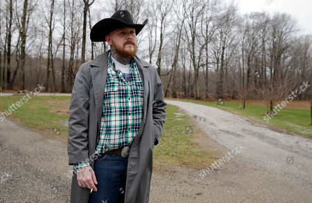 """Shane Johnson poses outside his home in Tippecanoe, Ind. Johnson was born into extremism. His father and many of his father's relatives were part of the Klan, he said, so there was only one real way for him to go as a youth. """"We were known as the Klan family,"""" he said. """"I got my first Klan robe when I was 14."""" He decided to quit after getting arrested, stopping drinking and meeting the woman who is now his wife"""