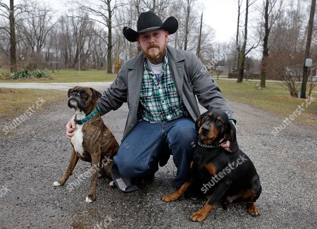 Shane Johnson poses with his dogs outside his home in Tippecanoe, Ind. Johnson was born into extremism. He eventually joined a skinhead group in addition to the KKK but finally decided to quit after getting arrested, stopping drinking and meeting the woman who is now his wife. Leaving was a real fight, though, as even relatives jumped him at a gas station one night after learning he wanted to quit