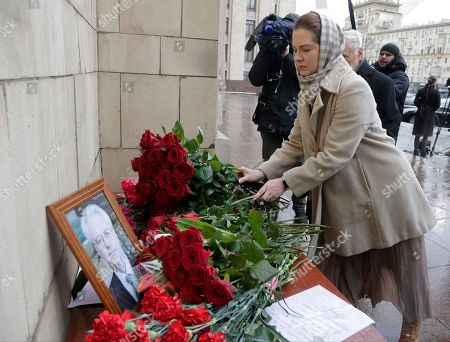People pay last respect as they put flowers to a portrait of the late Russian Ambassador to the United Nations Vitaly Churkin, outside the Foreign Ministry headquarters in Moscow, Russia, . Churkin died suddenly Monday after falling ill at his office at Russia's U.N. mission is being remembered by his diplomatic colleagues as a powerful and passionate voice for his nation