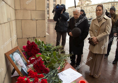 People pay last respects as they put flowers to a portrait of the late Russian Ambassador to the United Nations Vitaly Churkin outside the Foreign Ministry headquarters in Moscow, Russia, . Churkin died suddenly Monday after falling ill at his office at Russia's U.N. mission is being remembered by his diplomatic colleagues as a powerful and passionate voice for his nation
