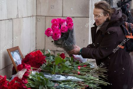 A woman pays her last respect as she offers flowers in front of the portrait of the Russian Ambassador to the United Nations Vitaly Churkin outside the Foreign Ministry headquarters in Moscow, Russia, . Churkin who died suddenly Monday after falling ill at his office at Russia's U.N. mission is being remembered by his diplomatic colleagues as a powerful and passionate voice for his nation
