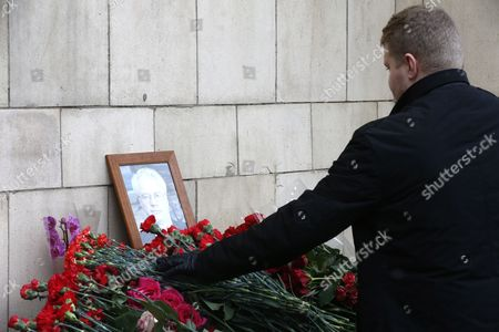 A man lays flowers near a portrait of late Russian Permanent Representative to the United Nations Vitaly Churkin at the Foreign Ministry headquarters in Moscow, Russia, 21 February 2017. Vitaly Churkin died suddenly in New York on 20 February.