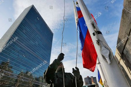 A United Nations security officer raises the Russian flag outside U.N. headquarters, Tuesday morning, . Vitaly Churkin, Russia's ambassador to the United Nations since 2006, died suddenly after falling ill at his office at Russia's U.N. mission Monday. He was the longest-serving ambassador on the Security Council, the U.N.'s most powerful body