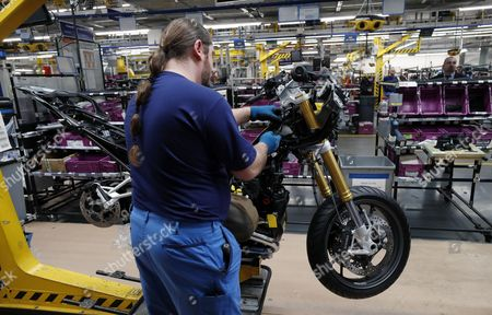 A man works on the assembly line BMW motorcycle factory in Berlin, Germany, 21 February 2017, as German Minister of Labour and Social Affairs, Andrea Nahles and French Minister of Labour, Myriam El Khomri (unseen) visit the plant. Both politicians also discussed the possible take over from the German Opel company by the French PSA Group that manufactures Peugeot and Citroen automobiles.