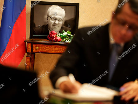 A picture of Vitaly Churkin, Russia's ambassador to the United Nations, is displayed while people sign condolences books at the Russian Mission to the U.N. in New York, . The city medical examiner was expected to perform an autopsy Tuesday on Russia's ambassador to the U.N., who died a day earlier after falling ill at his office at Russia's U.N. mission