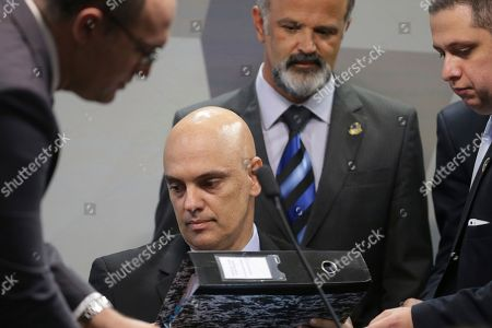 Brazil's former Minister of Justice Alexandre de Moraes, center, is surrounded by advisers during his arrival to meet of the Commission of Constitution and Justice of the Senate, in Brasilia, Brazil, . Brazil's Senate has begun a process that is likely to confirm Moraes for the country's highest court